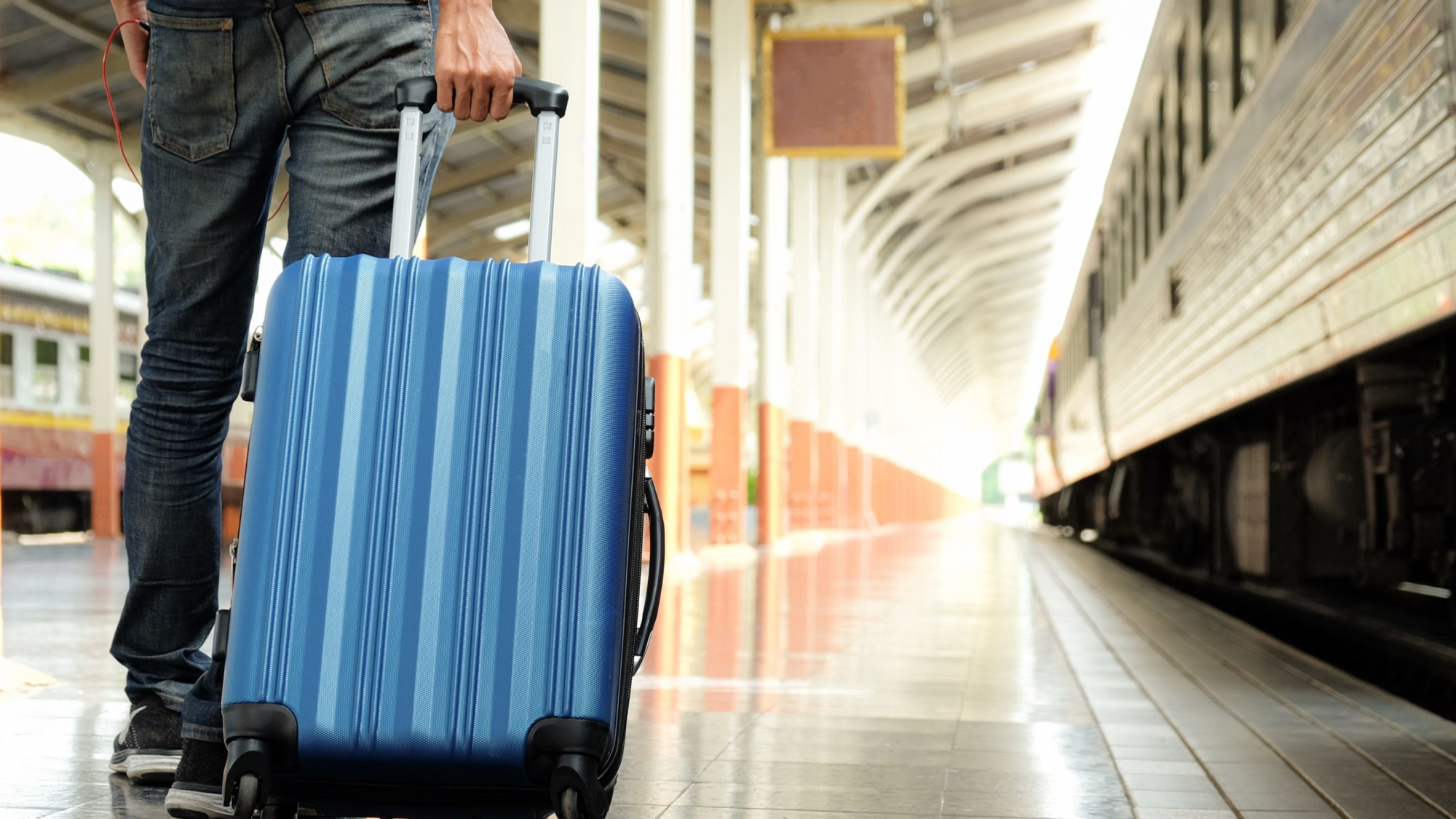 Travel concept,Traveler with a blue suitcase is waiting for the train.