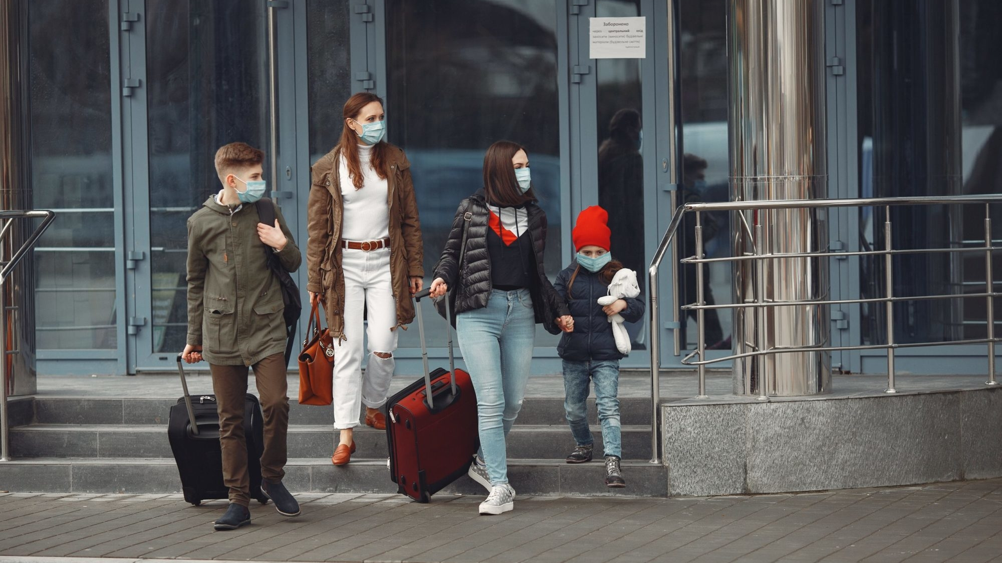 Travelers leaving airport are wearing protective masks.