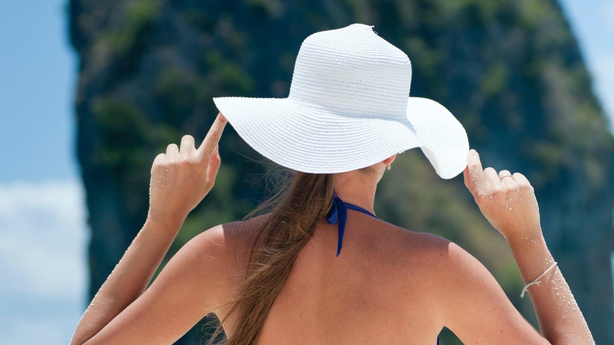 woman-in-blue-bikini-set-wearing-white-sun-hat-in-front-of-1007679