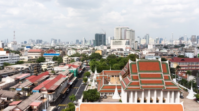 Aerial view of cityscape of Bangkok with old historic temples and modern skyscrapers under cloudy sky